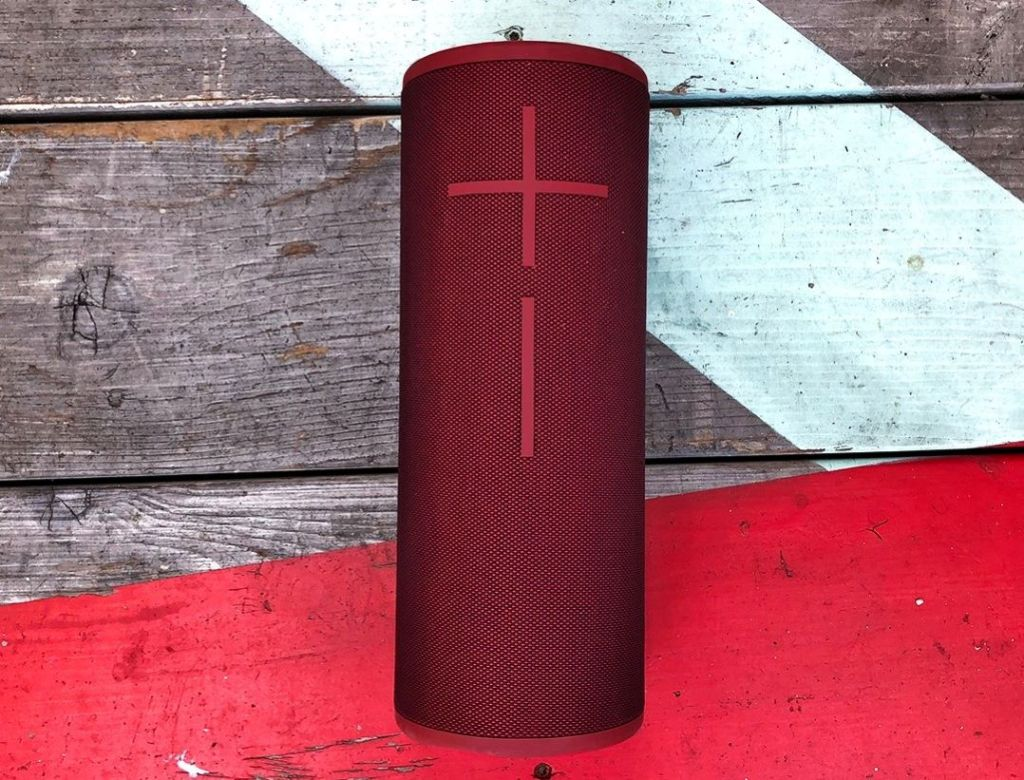 red portable speaker on a wooden table