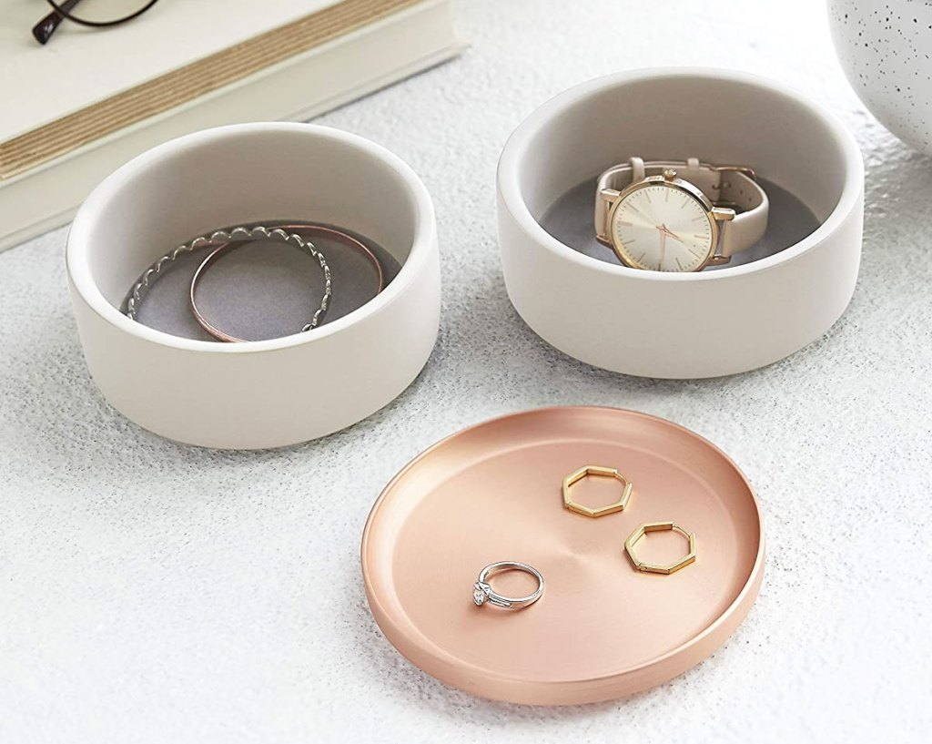 two white round jewelry boxes with a rose gold lid with rings and watches in them