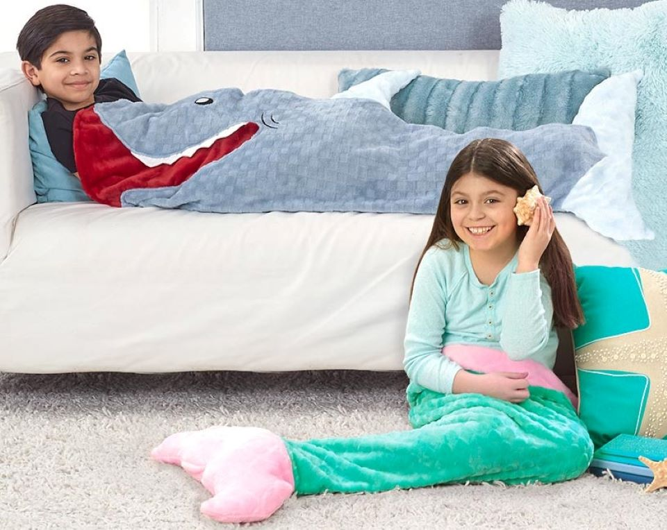 boy in a shark blanket on a couch next to a girl in a mermaid blanket on the floor