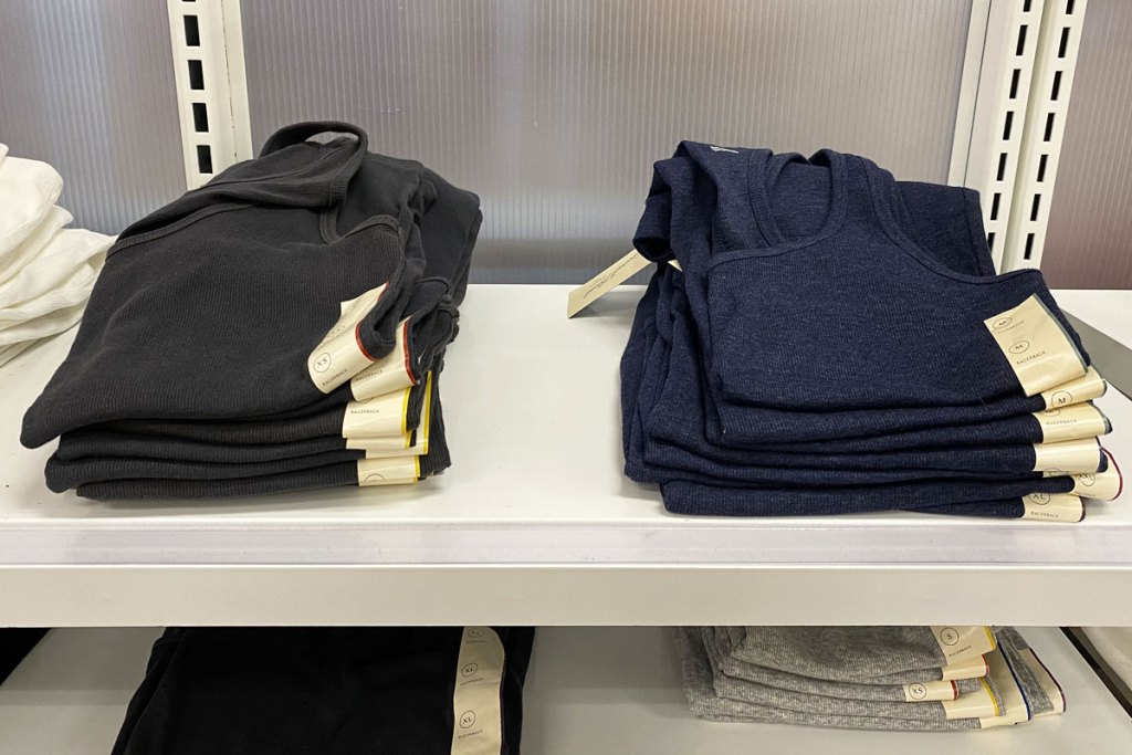 two piles of black and navy blue women's basic tank tops folded on white display shelf at target