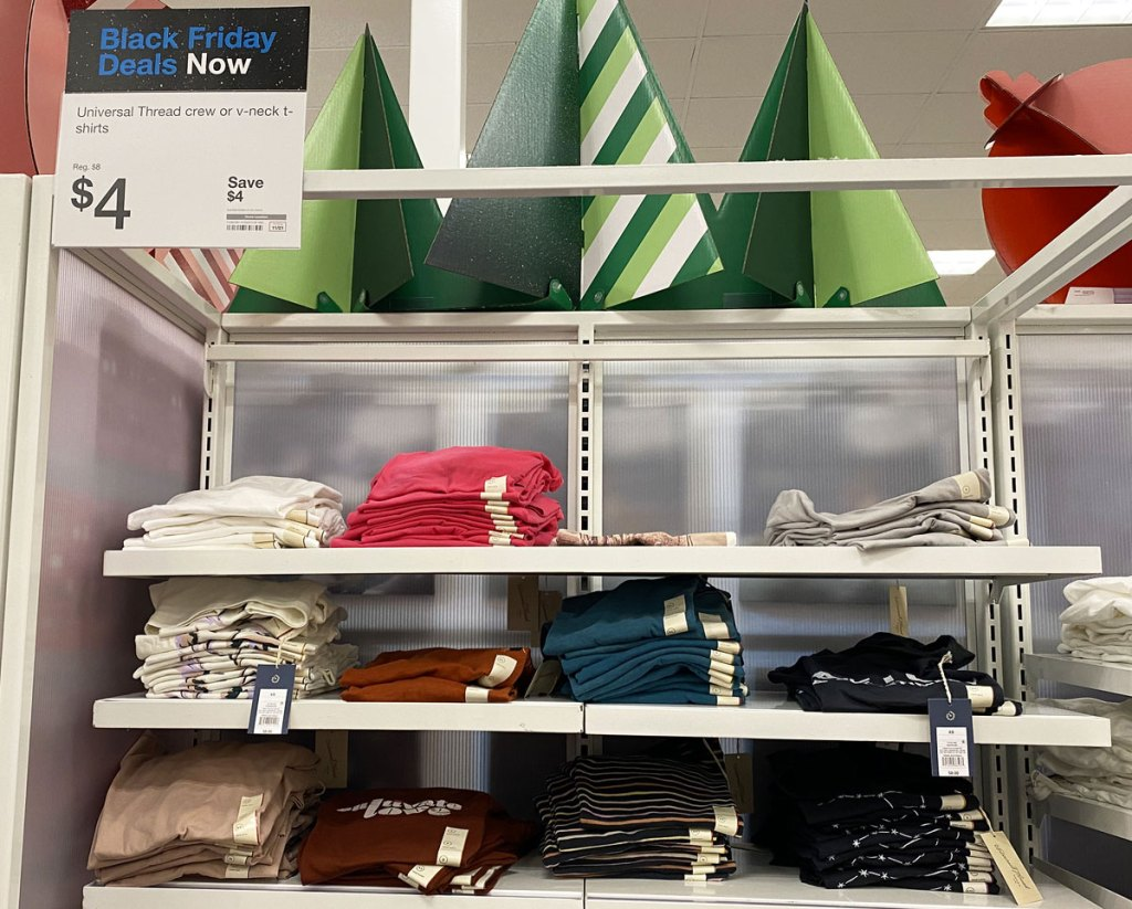white shelves full of various colors of women's basic tank tops with $4 sale sign at target