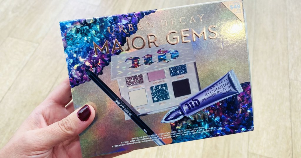 woman with dark red nails holding up the urban decay major gems makeup gift set