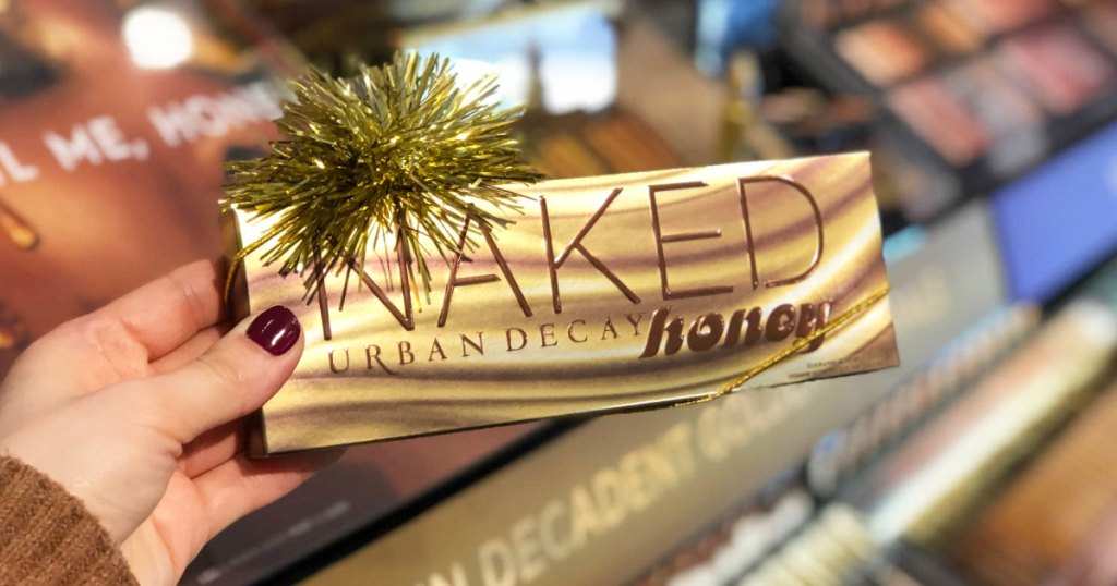 woman holding up an Urban Decay Naked Honey eyeshadow palette with a gold bow on top of it