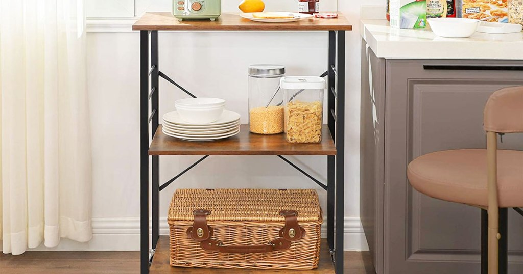 three tier kitchen cart with picnic basket at bottom, plates and sotrage containers on second shelf, and toaster on top