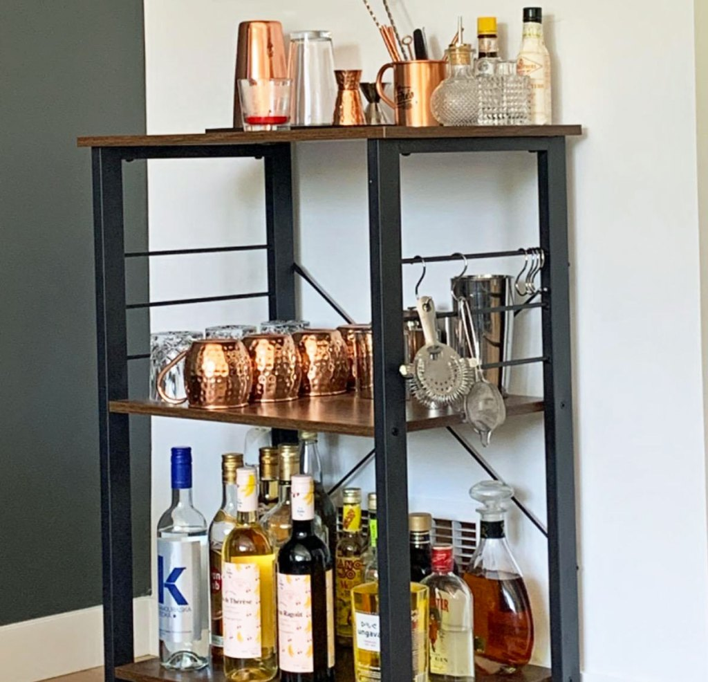 three tier kitchen cart against white wall with bottles of alcohol on bottom shelf, glasses on second shelf, and drinkware accessories on top shelf