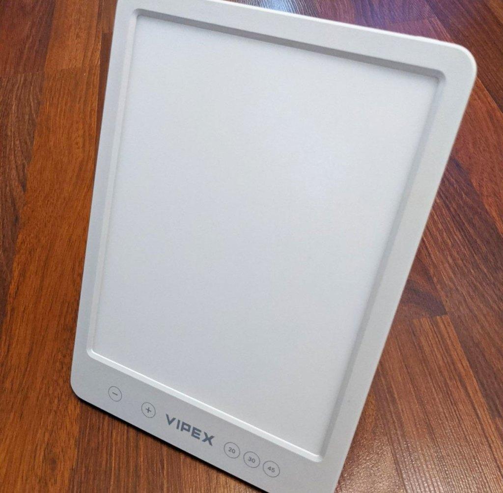 white rectangular light therapy lamp on wood floor