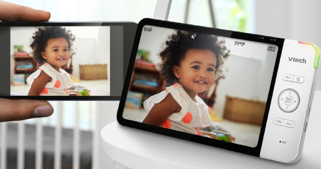 baby monitor and hand holding cell phone showing footage from monitor