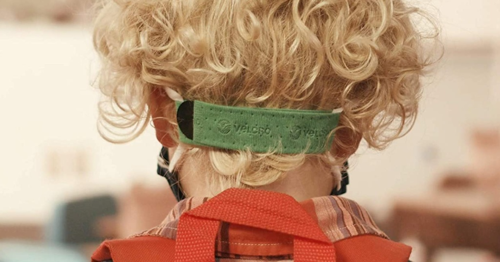 blonde haired child wearing face mask with green extender strap