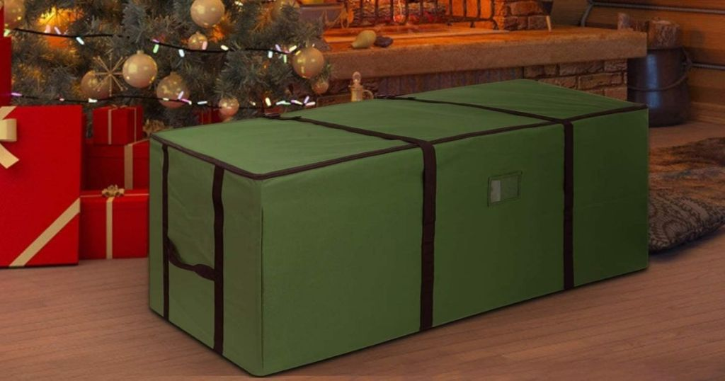 large green Christmas tree storage bag in front of decorated Christmas tree