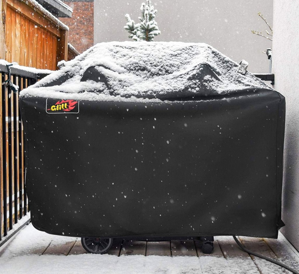 black grill cover over propane grill on deck covered in snow