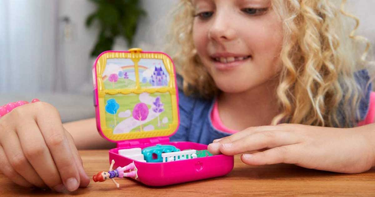 girl playing with polly pocket compact toy set and doll