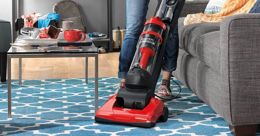woman vacuuming living room with red vacuum