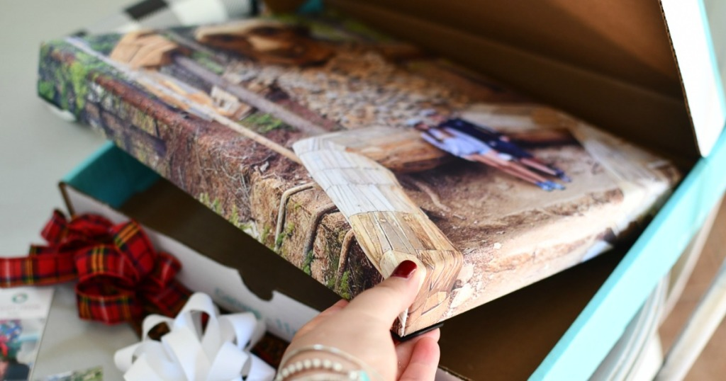 woman taking photo canvas out of box
