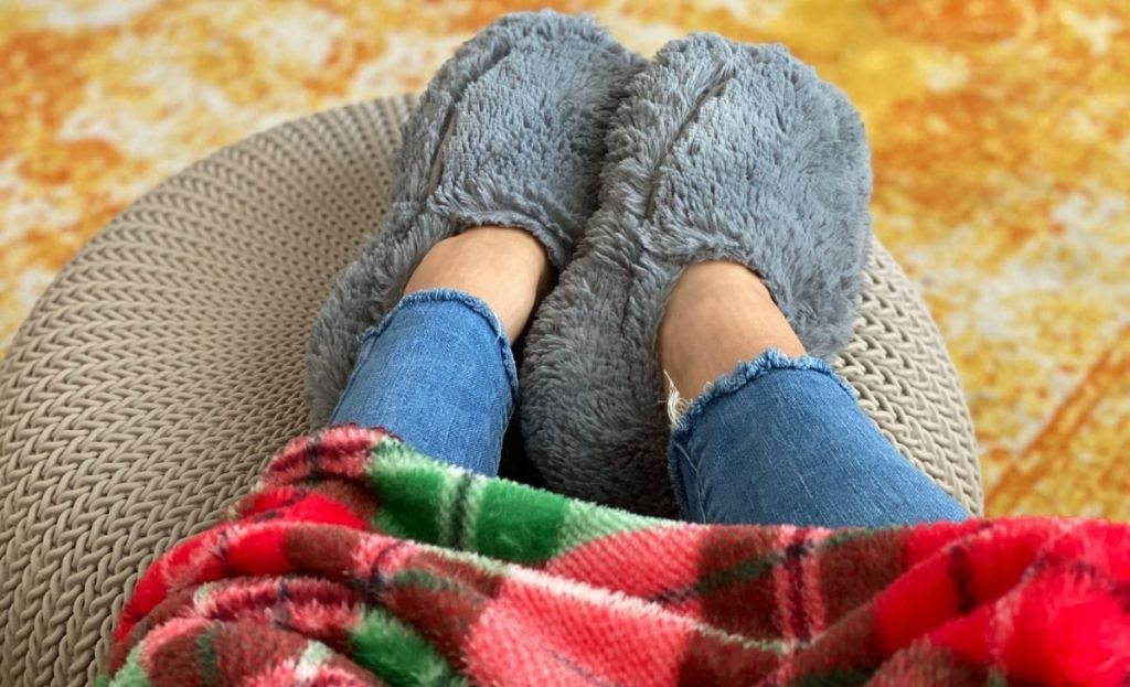A person in slippers with feet resting on an ottoman