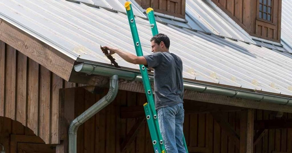 Man on a Werner Extension Ladder against a house with a metal roof