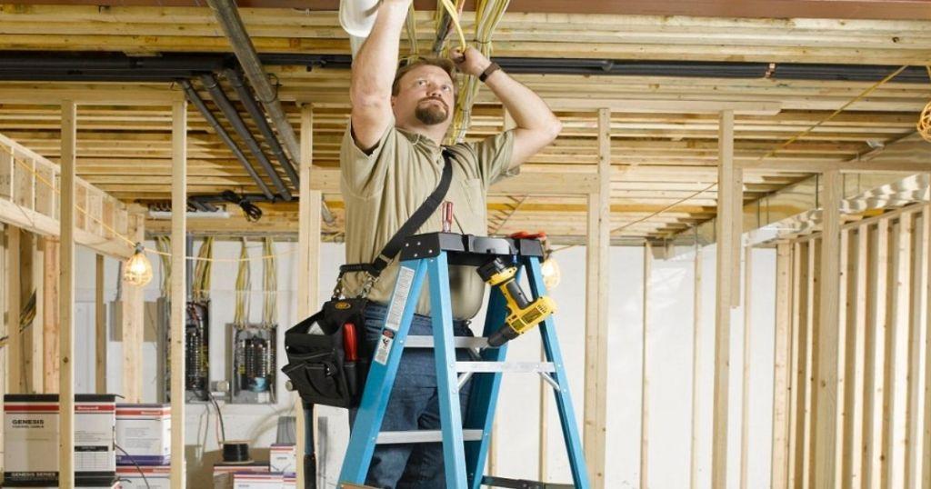 Man on blue 6-ft Werner ladder in an unfinished basement