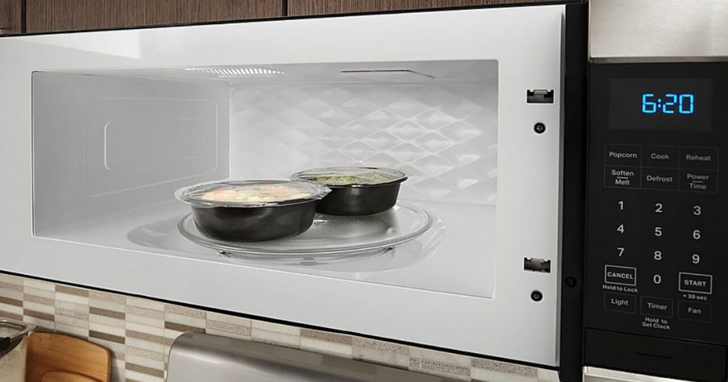 open microwave with food containers inside
