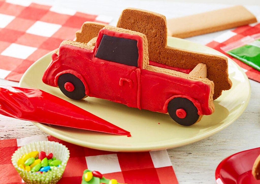 red gingerbread truck kit on plate with red frosting and candies