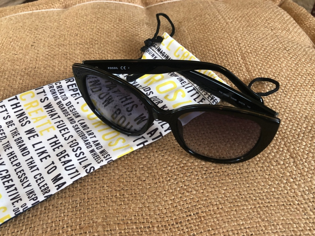 women's fossil sunglasses folded sitting on a fossil dustbag
