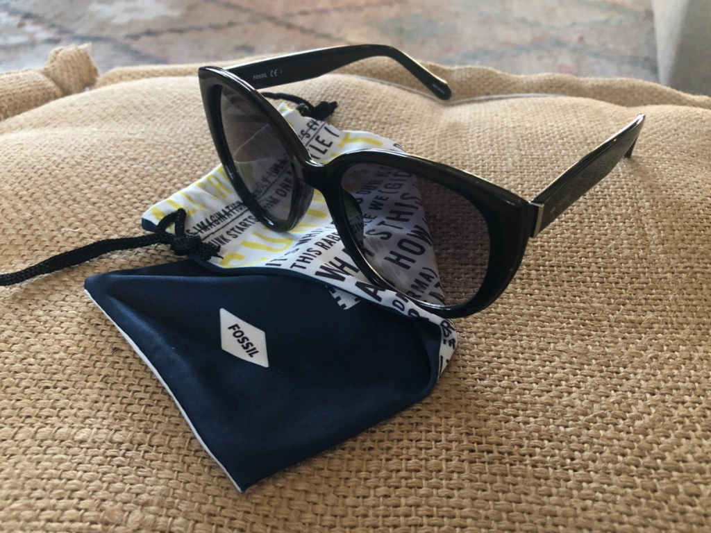 women's fossil sunglasses sitting on top of a fossil dust bag