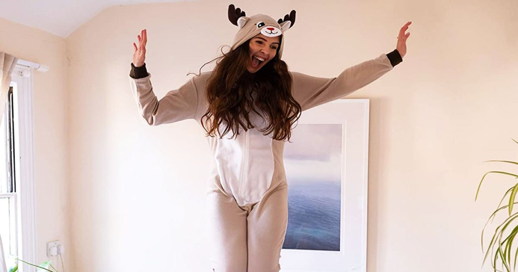woman jumping on a bed wearing a pair of of reindeer one-piece pajamas