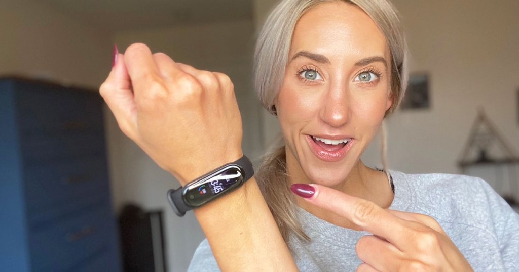 woman with blonde hair wearing a grey sweatshirt holding up her wrist with a black fitness tracker on it and pointing at it with other hand