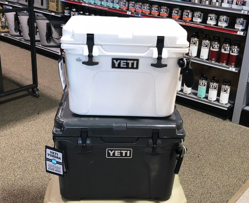 a smaller white yeti cooler stacked on top of a black one with shelves of yeti products in the background