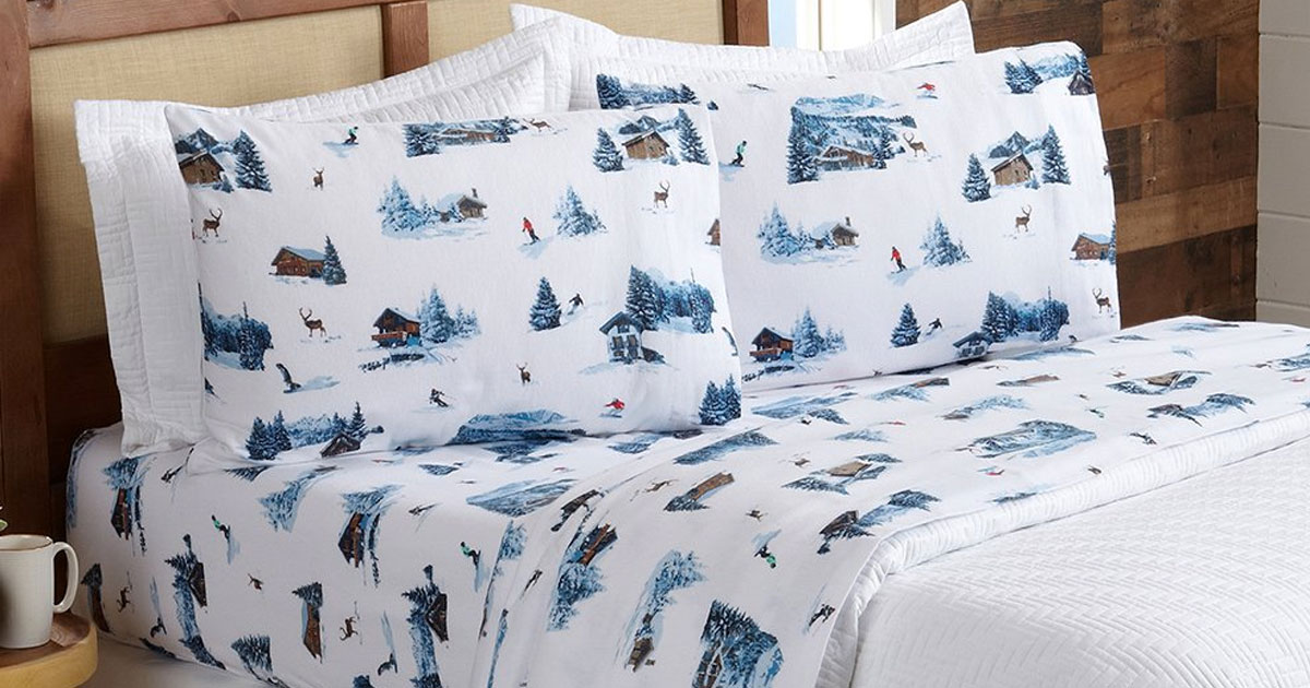 bed made with white flannel sheet set with blue snowy cabins printed on them