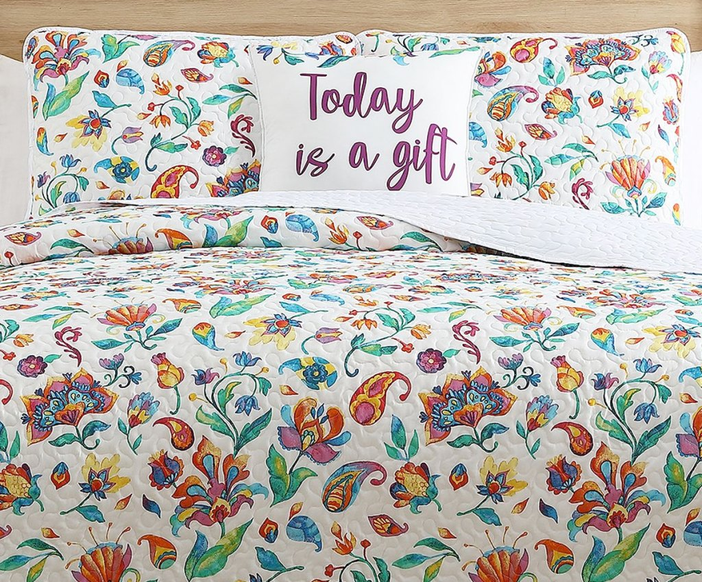 white quilt set with bright flower and paisley print with matching shams and throw pillow
