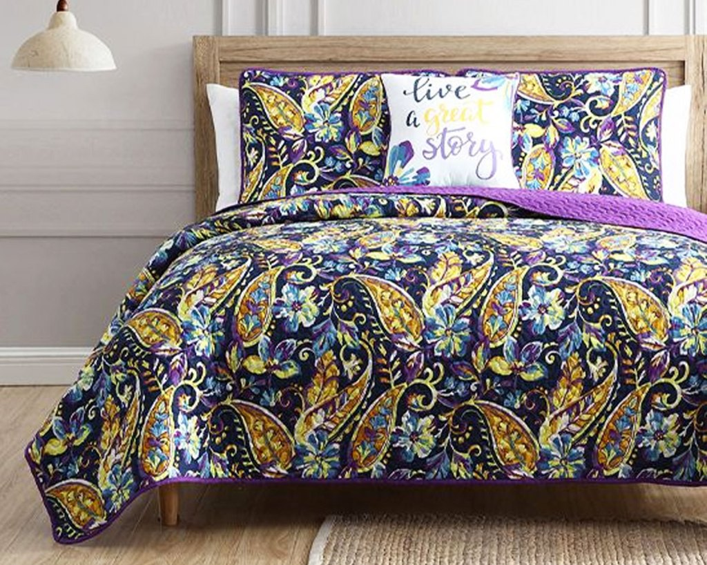 purple, yellow, and blue paisley print quilt set on bed with matching pillow shams and throw pillow