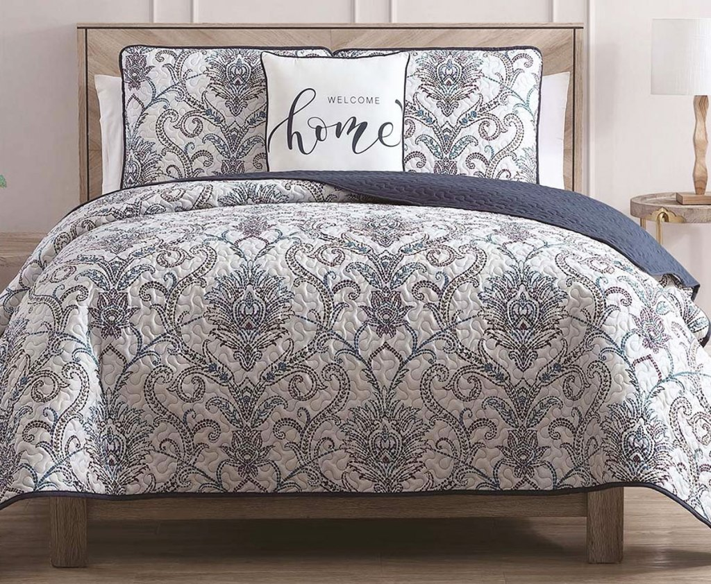 grey and white prnt quilt set on bed with matching pillow shams and throw pillow