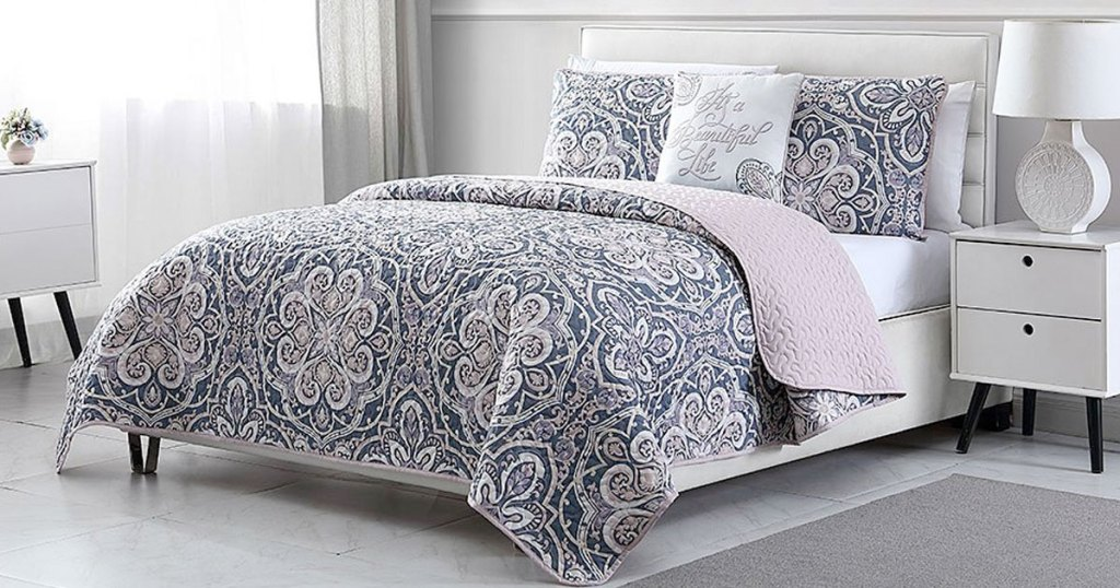 grey and navy blue print quilt set on bed with matching pillow shams and coordinating throw pillow