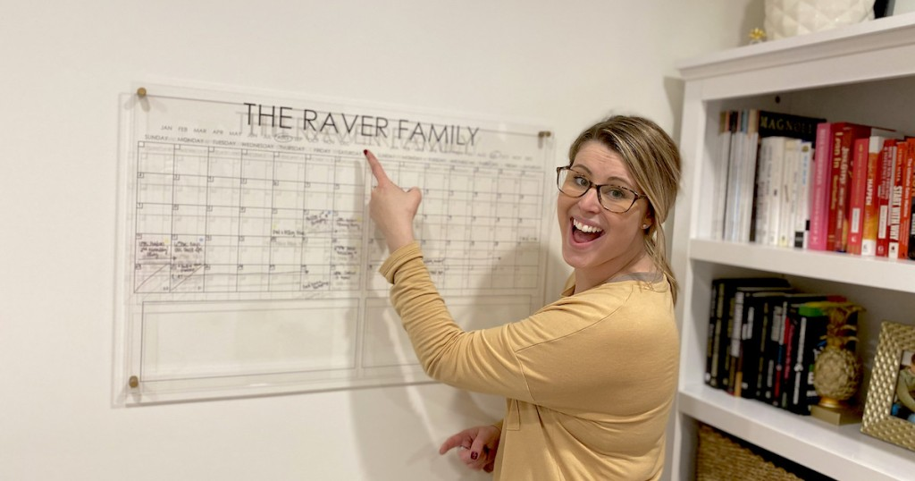 woman pointing to clear acrylic calendar on wall