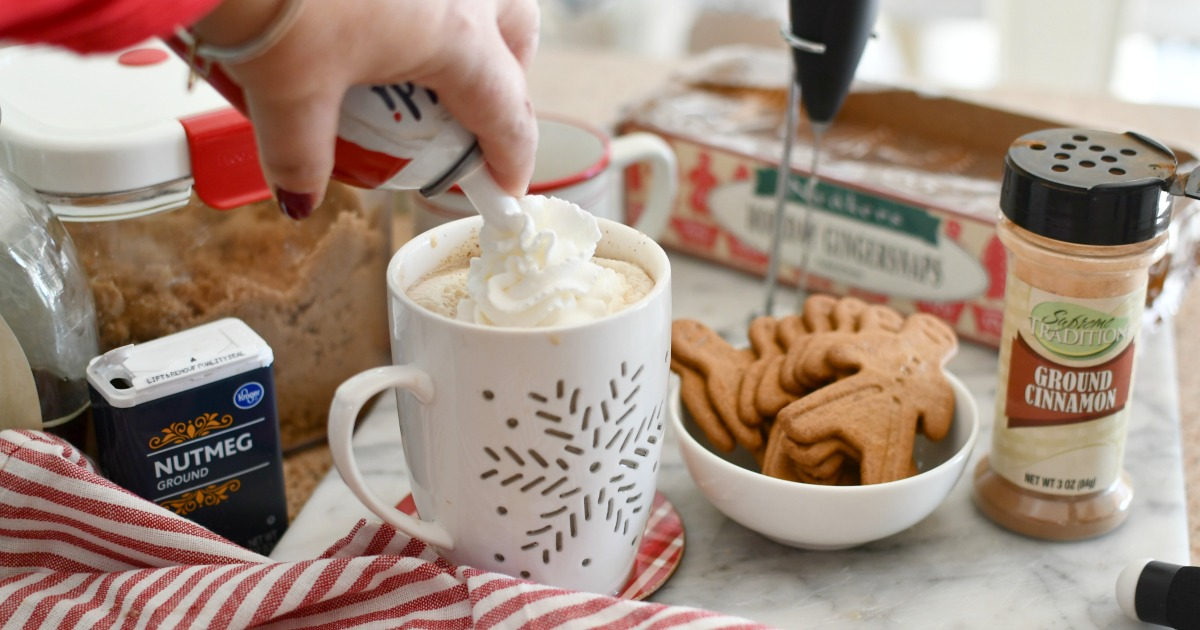 adding whipped cream to latte