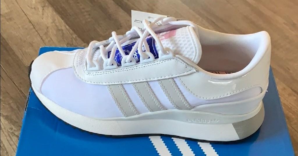 sepatu wanita putih, abu-abu, biru, dan merah muda di atas kotak sepatu biru