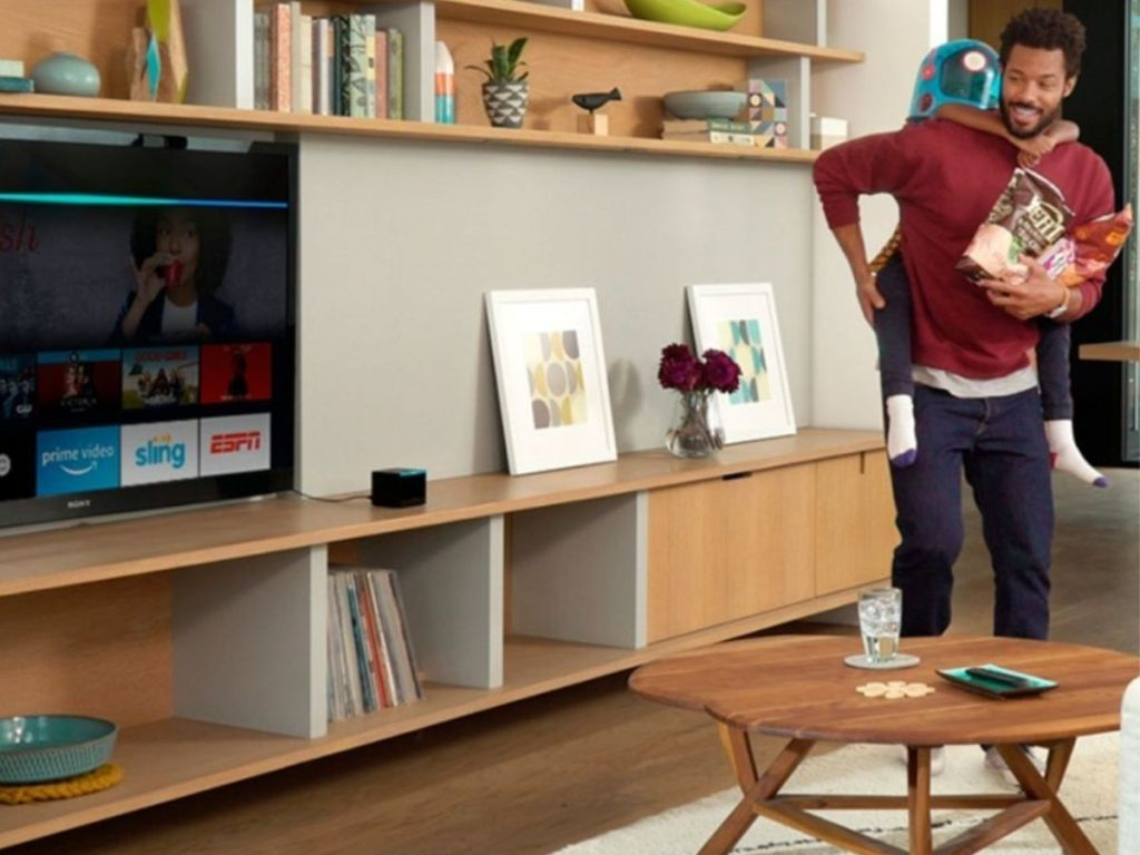 man giving boy piggy back ride in living room with amazon fire cube sitting next to televsion
