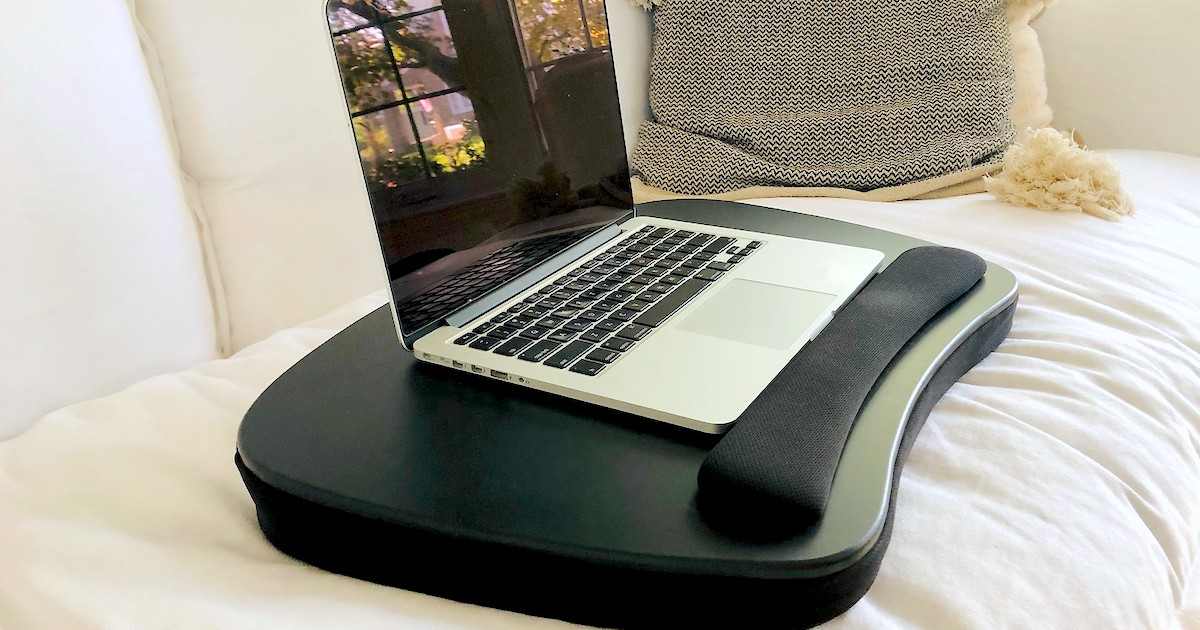 black lap desk with laptop on top sitting on white couch