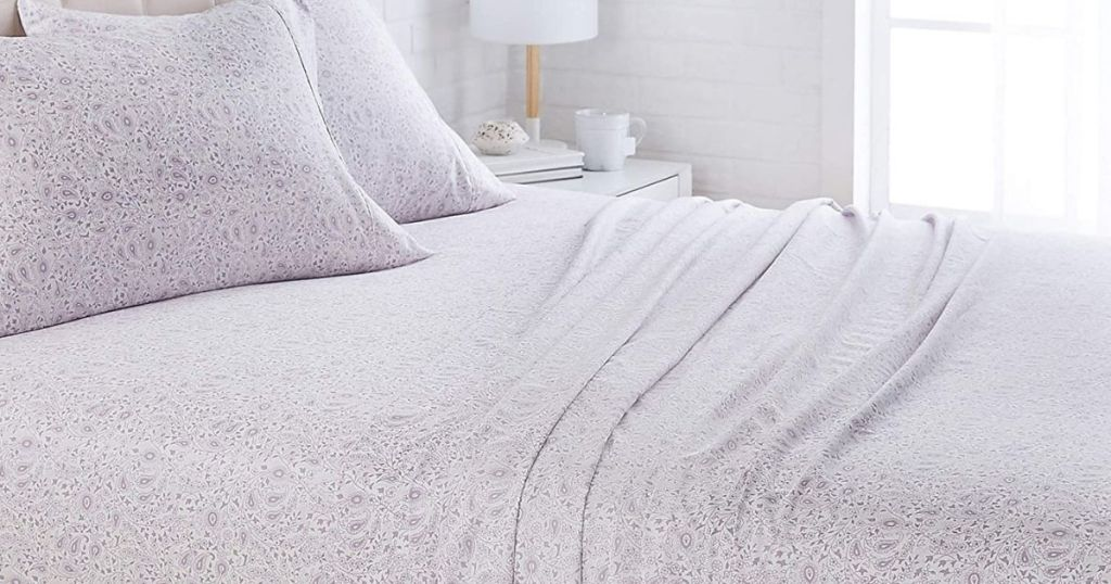 purple floral bed sheets on bed