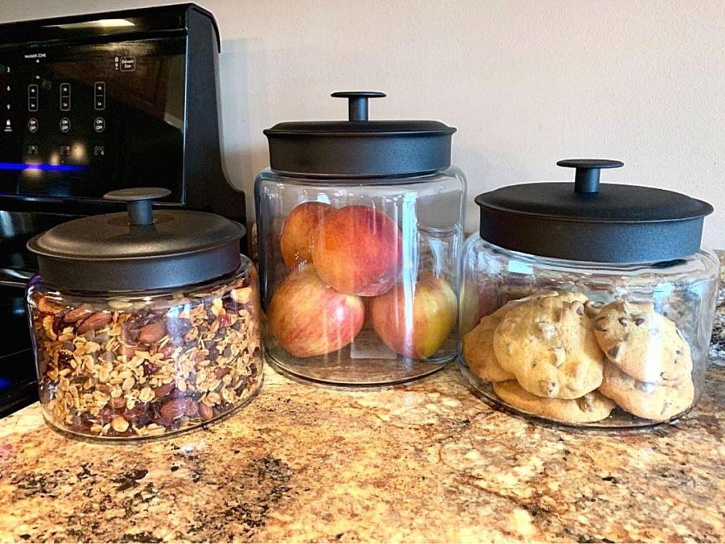 three glass jars with black lids