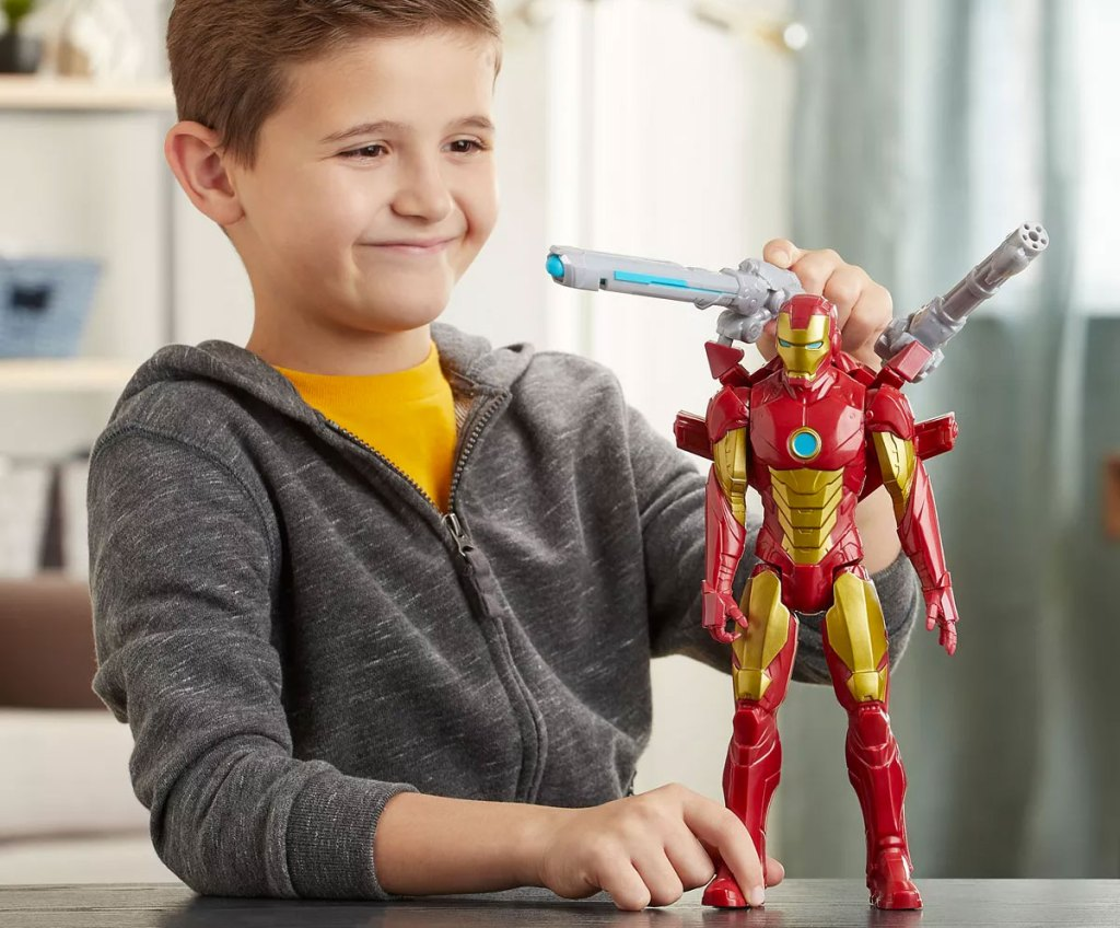 boy in grey sweatshirt playing with large iron man action figure on table