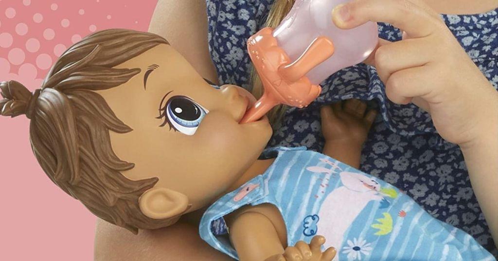 girl feeding baby alive doll