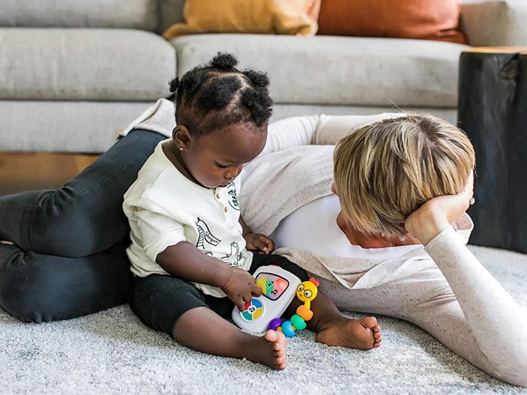 wanita dan bayi di lantai bermain dengan mainan
