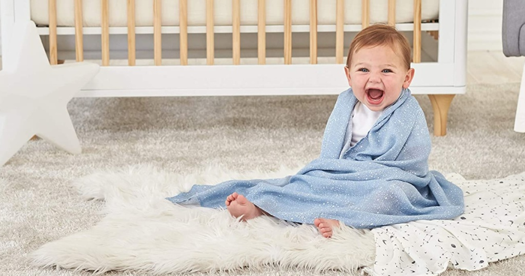 baby in blue blanket next to crib