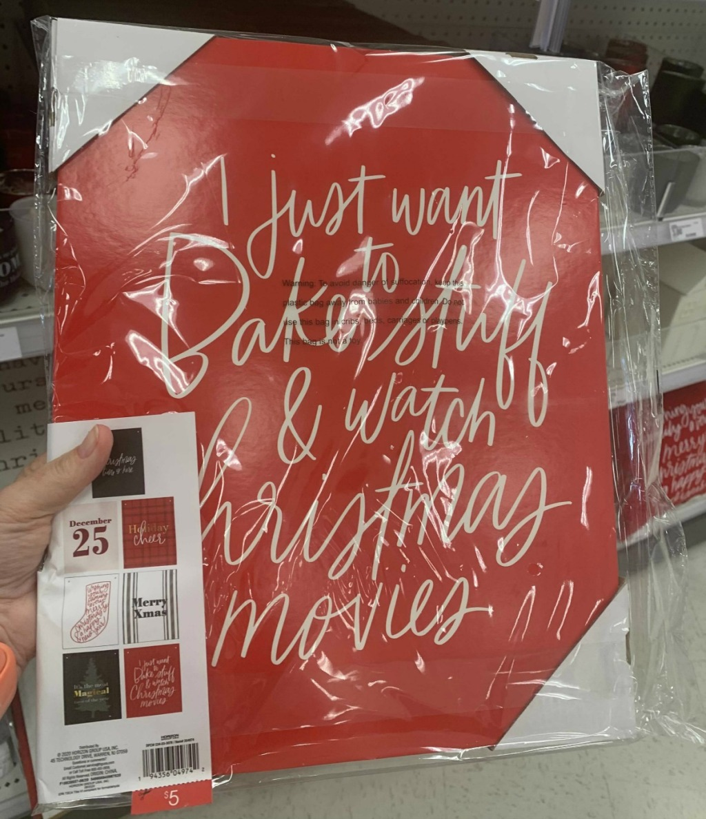 hand holding a red christmas sign in store