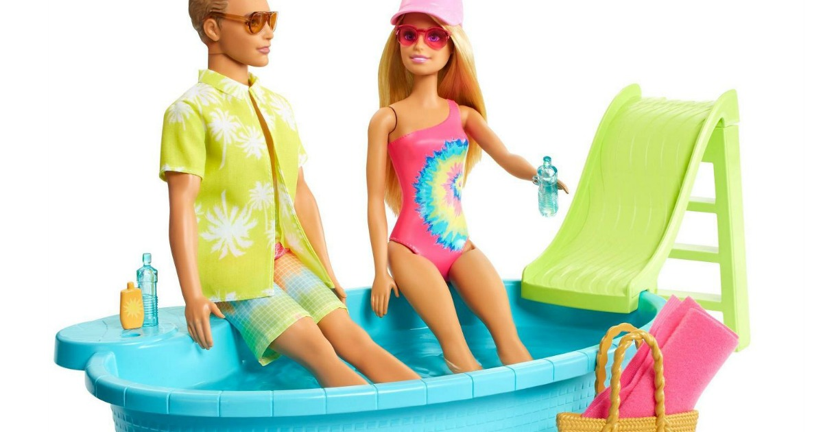 stock image of barbie and ken dolls sitting in a toy swimming pool