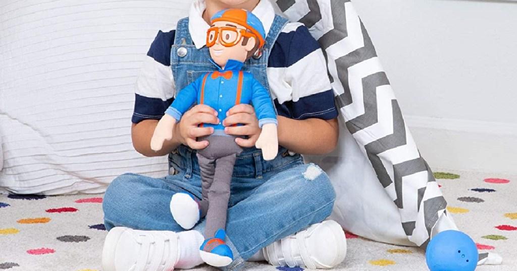 boy holding blippi doll