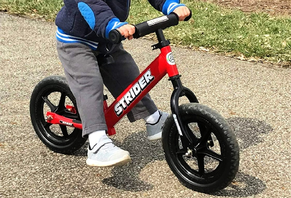 boy riding Strider 12 Balance Bike in red