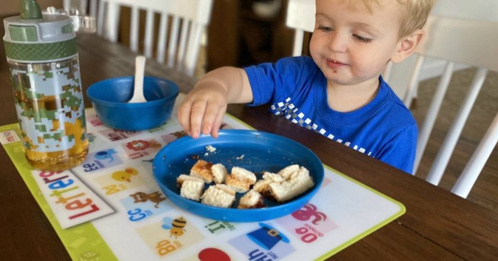 boy eating with educational placemat