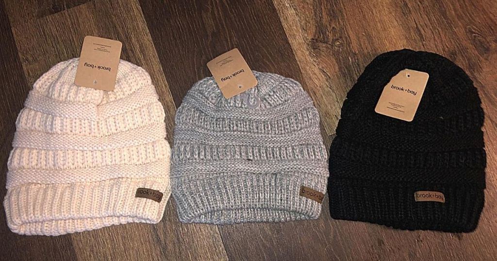 white gray and black beanies on hardwood surface