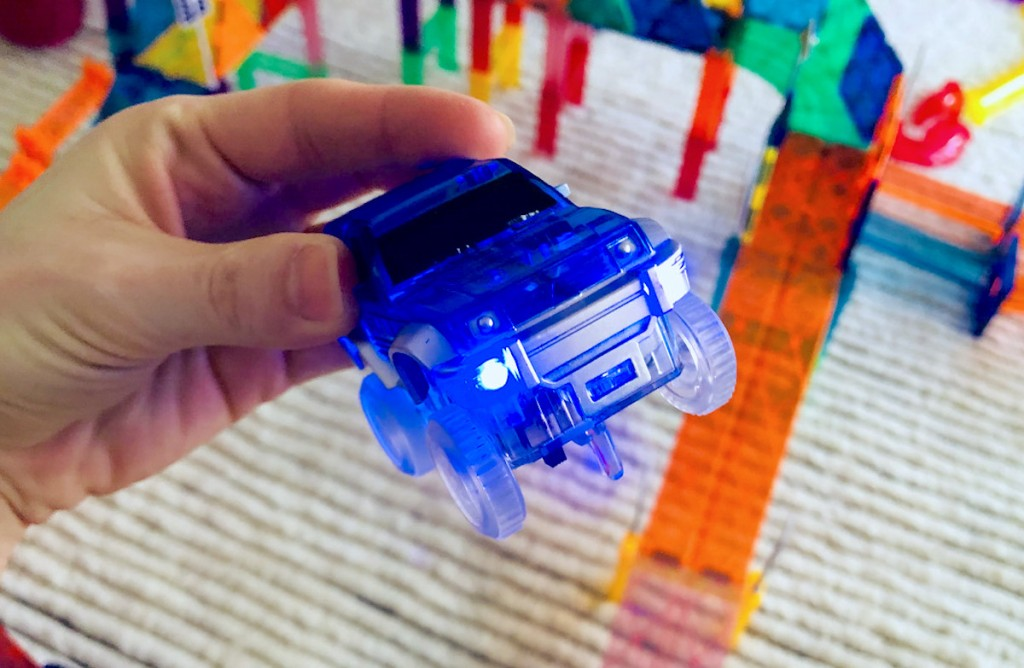 hand holding blue toy truck with lights on